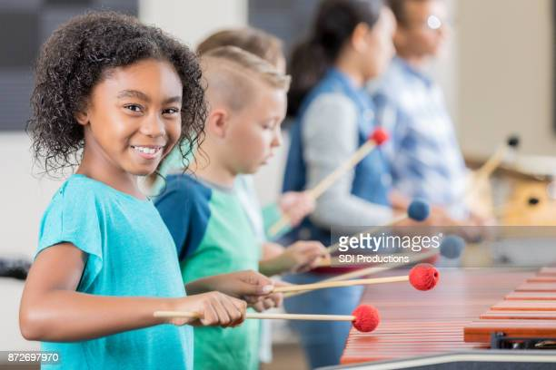 Adorable little girl smiles for camera while playing xylophone