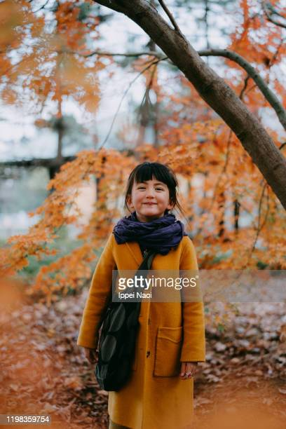 adorable little girl smiling at camera with autumn leaves, tokyo - ippei naoi stock pictures, royalty-free photos & images