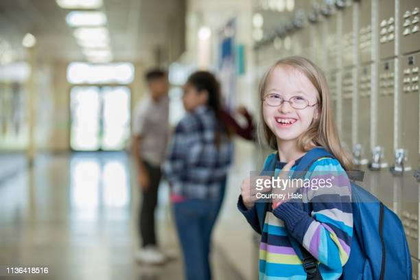 adorable little girl with down syndrome smiles on her first day of junior high school - charter_school stock pictures, royalty-free photos & images