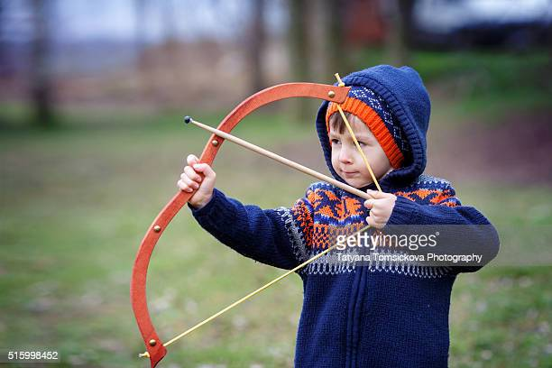 Adorable little preschool boy, shoot with bow and arrow at target in open air, springtime outdoors
