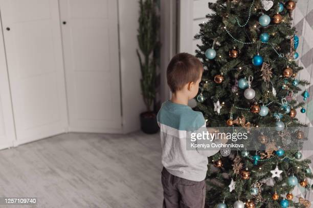 adorable little smiling kid boy holding christmas tree. happy child in winter clothes, hat, gloves choosing xmas tree in outdoor shop. family, tradition, celebration concept - happy new month stock pictures, royalty-free photos & images