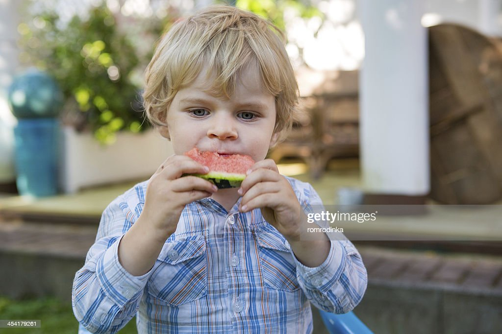 Adorable little toddler boy with blond hairs eating watermelon i : Stock Photo