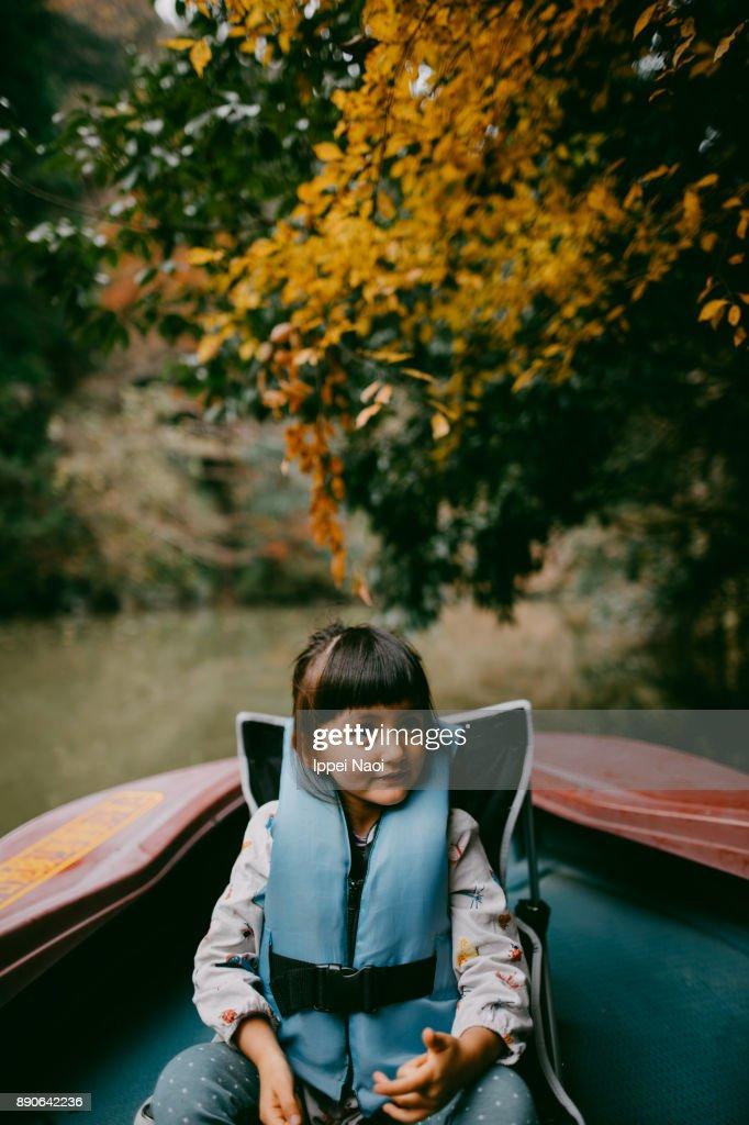 Cute Eurasian girl enjoying a boat ride with autumn foliage