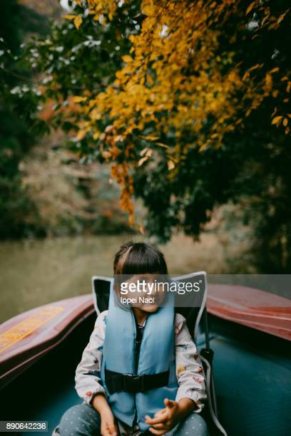 Adorable mixed race girl enjoying a boat ride with autumn foliage