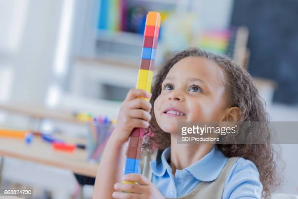 Adorable mixed race girl uses counting blocks