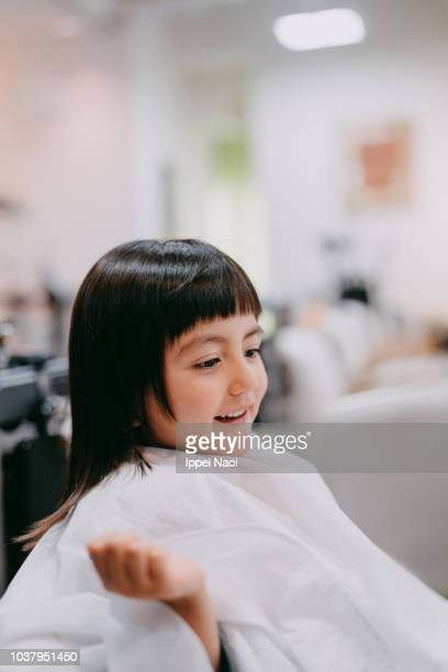 Adorable mixed race little girl at hairdresser