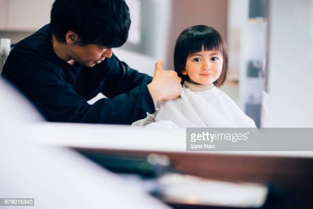 Adorable mixed race little girl at hairdresser