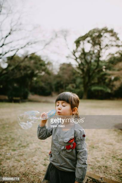 Adorable mixed race little girl blowing bubbles in park