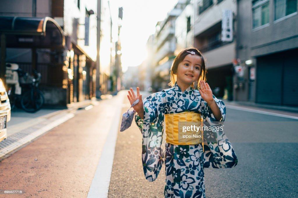 Adorable mixed race little girl in yukata dancing in the street, Tokyo : Stock Photo