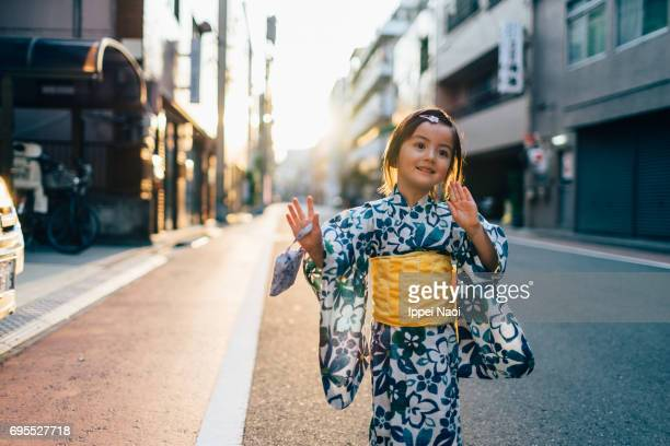 Adorable mixed race little girl in yukata dancing in the street, Tokyo