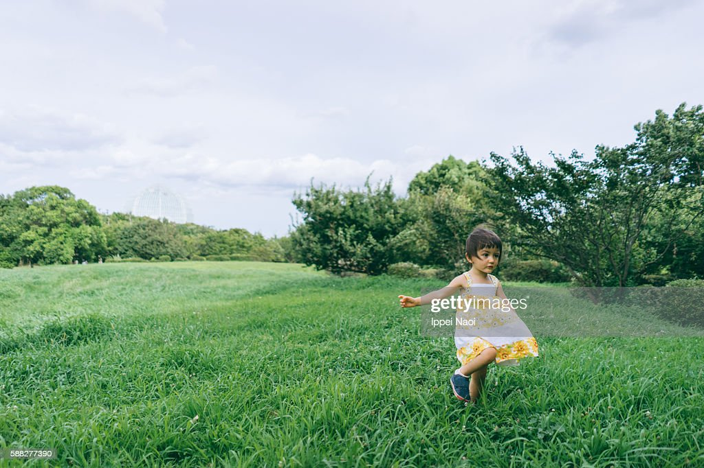 Adorable mixed race little girl running around grassy meadow : ストックフォト