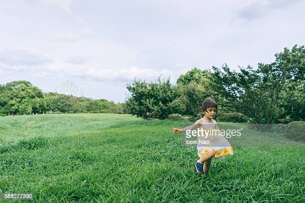 Adorable mixed race little girl running around grassy meadow