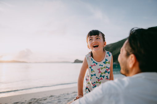 Adorable mixed race preschool girl laughing on beach at sunset, Okinawa, Japan - gettyimageskorea