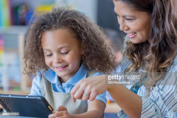 Adorable mixed race student uses digital tablet
