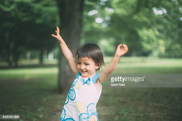 Adorable mixed race toddler girl having fun at park