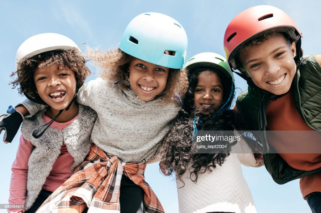 Adorable multi-ethnic group of kids wearing helmets and looking to the camera with happiness : Stock Photo