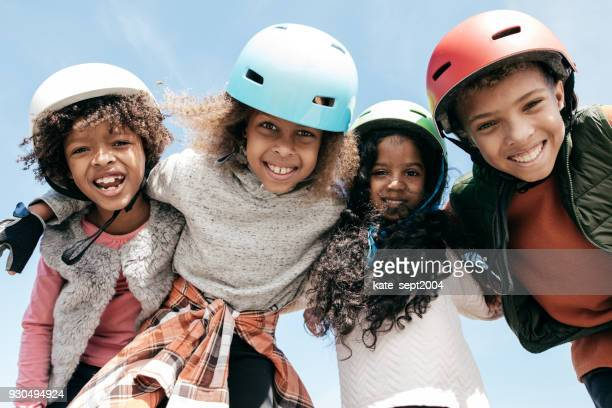 adorable multi-ethnic group of kids wearing helmets and looking to the camera with happiness - cycling helmet stock pictures, royalty-free photos & images