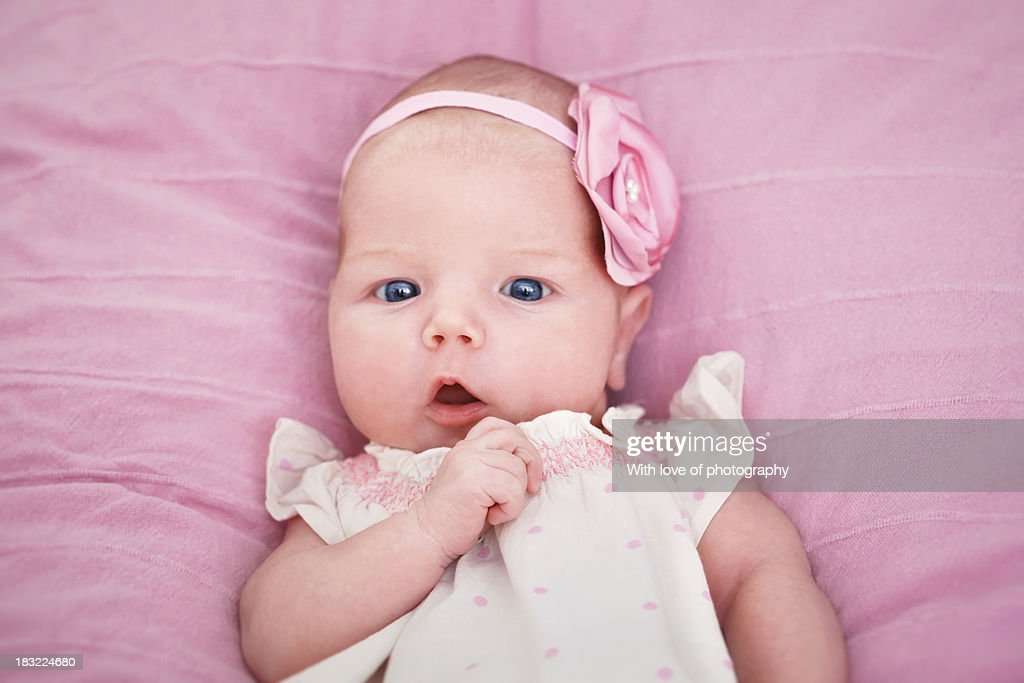 Adorable newborn baby girl in pink stock photo