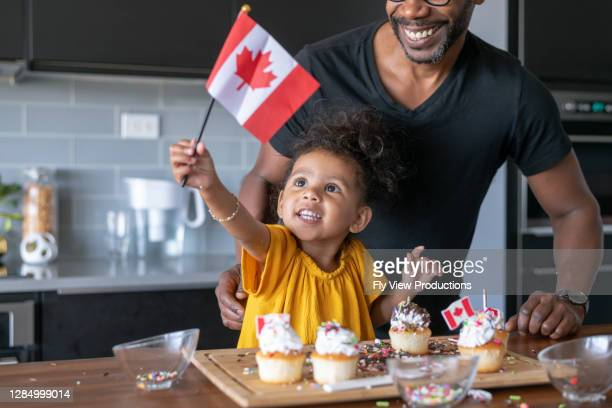 adorable preschool age girl and father celebrating canada day at home - canada day stock pictures, royalty-free photos & images