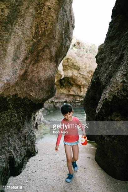 Adorable preschool girl playing on beach in cave, Okinawa, Japan