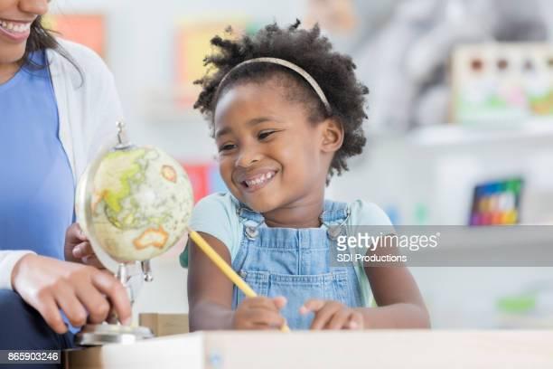 Entzückende Vorschul Mädchen studiert einen Globus