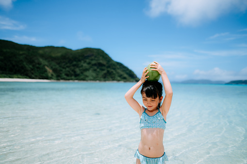 Adorable preschool girl with coconut on tropical beach, Okinawa, Japan - gettyimageskorea
