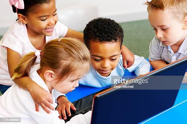 Adorable preschoolers using laptop computer