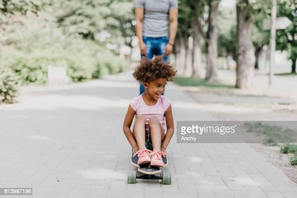 Adorable preschoolg girl is sitting on the longboard skateboard