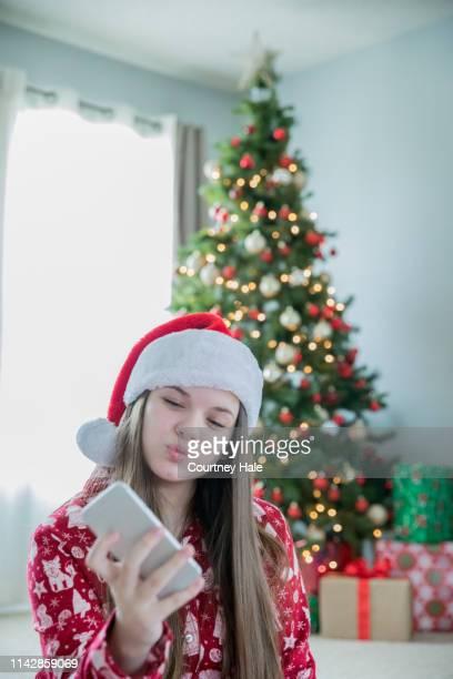 Adorable chica preadolescente tomando selfie con nuevo teléfono inteligente en la mañana de Navidad