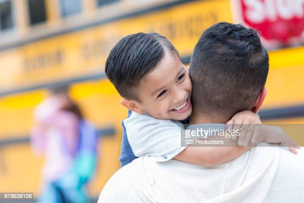adorable schoolboy hugs his dad after getting off school bus - first day of school stock pictures, royalty-free photos & images