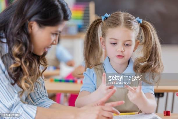 Adorable schoolgirl counts on fingers in class