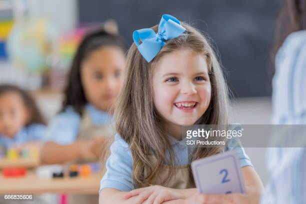 adorable schoolgirl learns math at school - hair bow stock pictures, royalty-free photos & images