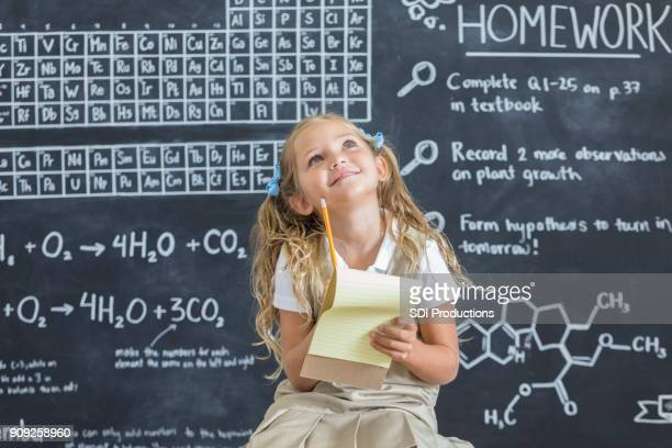 Adorable schoolgirl thinks while in science class