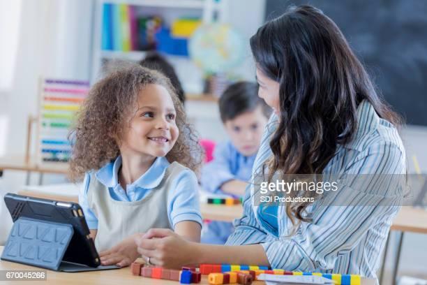 Adorable schoolgirl uses digital tablet at school
