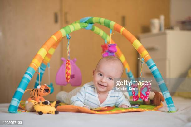 adorable smile on a little baby boy face while playing on a bed - toy rattle stock pictures, royalty-free photos & images