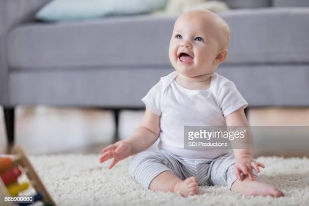 adorable bebé sonriente sentada en el piso y mirando hacia arriba - bebé fotografías e imágenes de stock