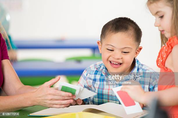 Adorable special needs boy works with therapist