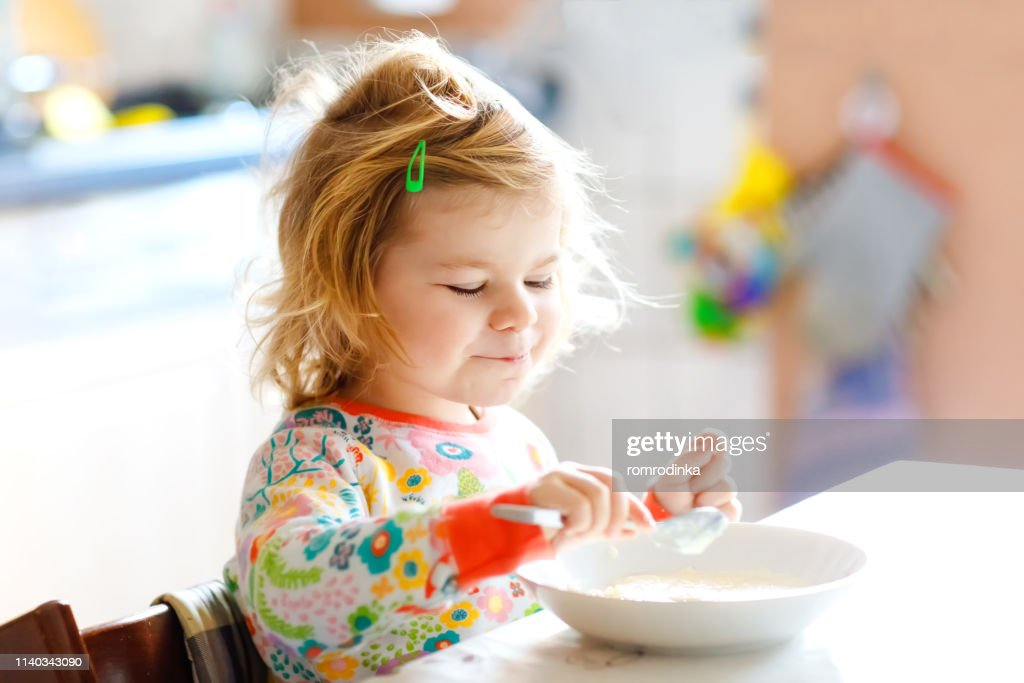 Adorable toddler girl eating healthy porridge from spoon for breakfast. Cute happy baby child in colorful pajamas sitting in kitchen and learning using spoon. : Stock Photo