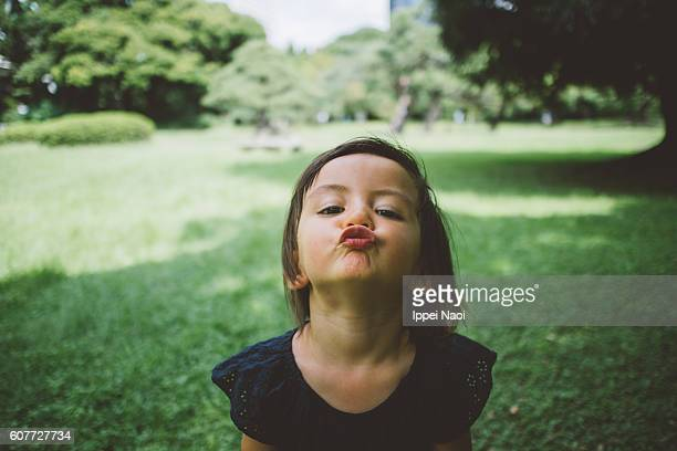 Adorable toddler girl making kissing lips toward camera