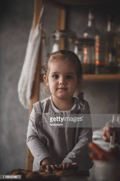 Adorable toddler girl playing with a rolling pin in the kitchen