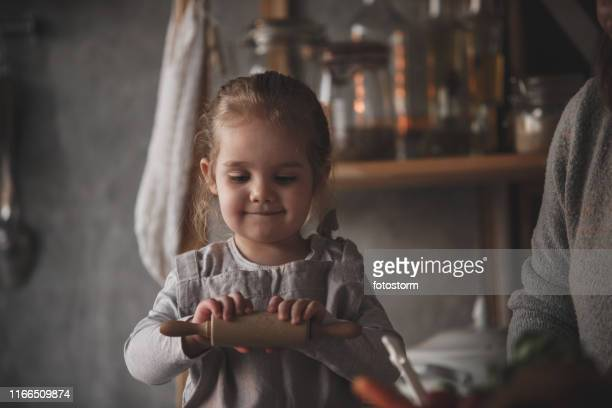 Adorable toddler girl with a rolling pin