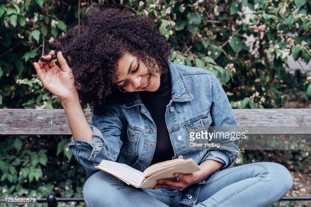 adorable young african american woman reading a good book while chilling on bench in park - lezen stockfoto's en -beelden