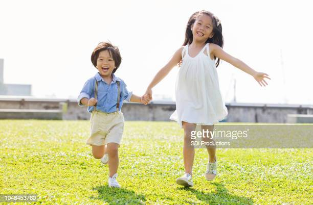 adorable young brother and sister running in grass - suspenders stock pictures, royalty-free photos & images