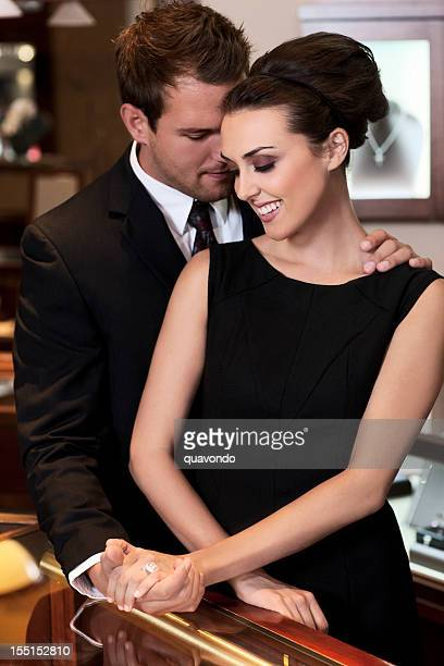 adorable young couple shopping for diamond ring in jewelry store - jewelry store stock pictures, royalty-free photos & images
