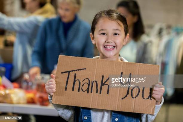 adorable young food bank volunteer holds 'thank you' sign - charity benefit stock pictures, royalty-free photos & images