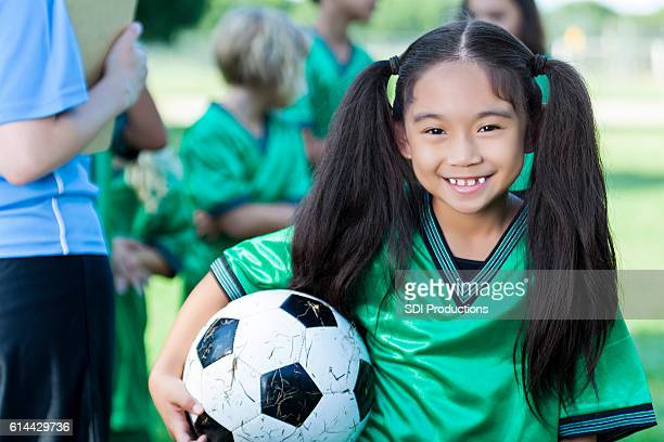 Adorable young girl holds soccer ball