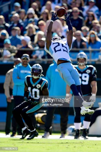 Adoree' Jackson of the Tennessee Titans tries to make an interception but the ball goes through his hands and is caught by Curtis Samuel of the...