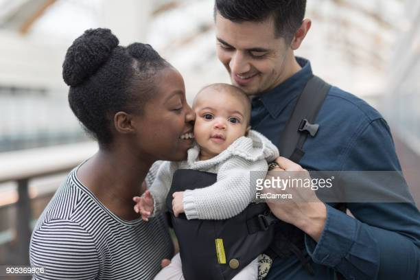 adoring parents with their baby in a shopping mall - african american family home stock photos and pictures