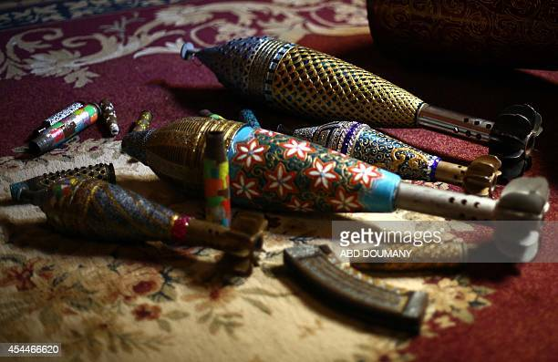 Adorned used and diffused ammunition rounds painted by Syrian artist Akram Abu AlFawz are seen on May 31 2014 in Douma a rebelheld town near Damascus...