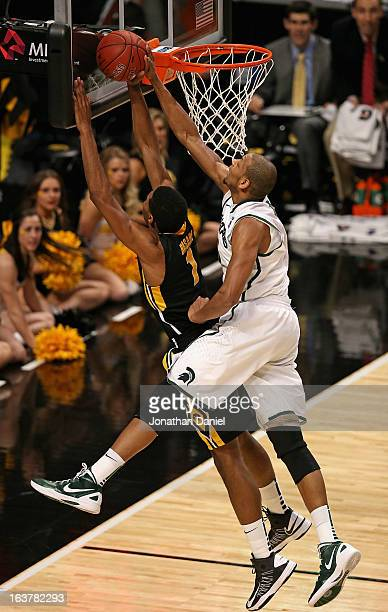 Adreian Payne of the Michigan State Spartans blocks a shot by Melsahn Basabe of the Iowa Hawkeyes during a quarterfinal game of the Big Ten...